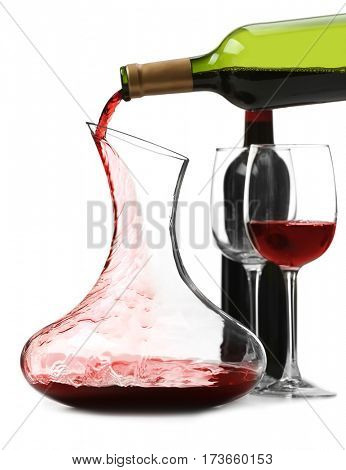 Pouring wine in carafe on white background