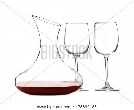Glass carafe of red wine and glasses on white background
