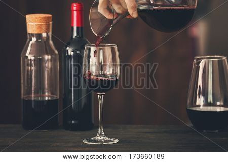Pouring wine in glass on wooden table