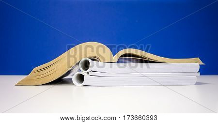 A brown book open side view on blue background