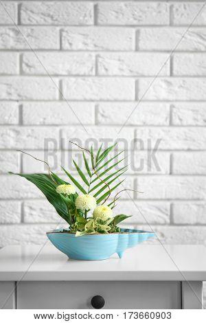 Flower arrangement on brick wall background