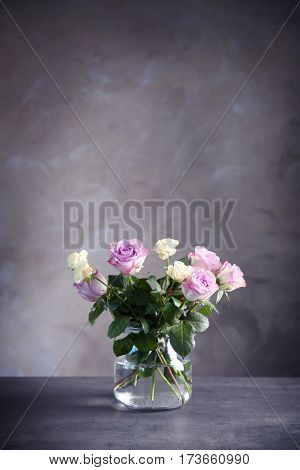 Glass vase with bouquet of beautiful roses on color background