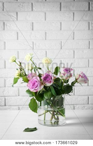 Glass vase with bouquet of beautiful flowers on brick wall background