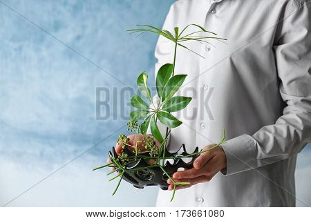 Woman holding floral composition on color background