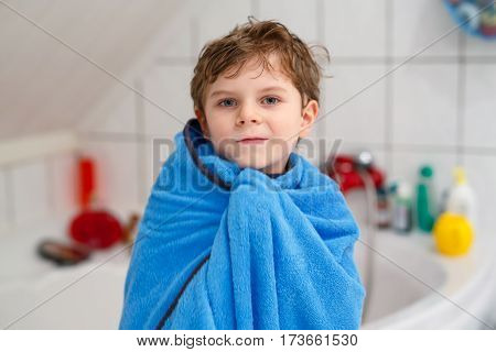 Happy little kid boy after taking bath wet and smiling. Adorable child with blond hairs taking bath and having fun.