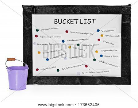 Bucket lists on the board. List on white board in a black velvet frame. The list of things to do pinned to the board. The commands in Polish. Next to the board purple bucket on completed tasks. The composition isolated on a white background with slight re