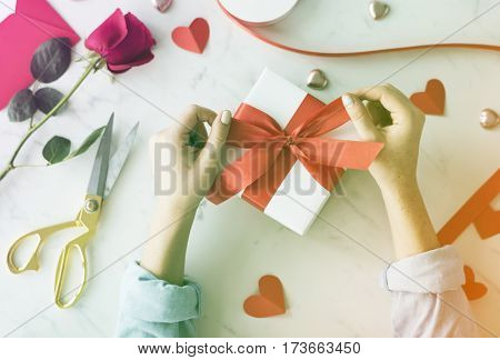 Hands tie ribbon on gift box