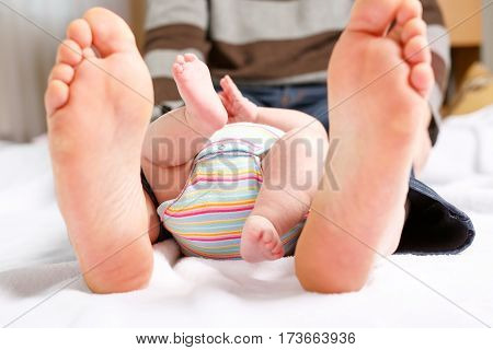 Closeup of huge feet of father and little newborn baby. Big feet of adult and tiny legs of child. Happy parenthood, carefree childhood, family, love, tenderness.