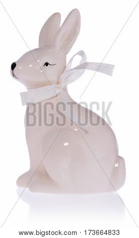 Ceramic white bunny with a bow. Easter bunny isolated on white background with a slight shadow and reflection.