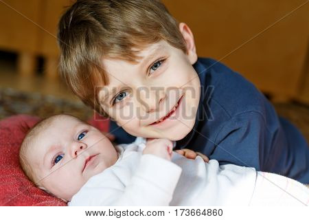 Close-up portrait of happy little kid boy with newborn baby girl, cute sister. Siblings. Brother and baby cuddling together. Kids bonding. Family of two bonding, love.