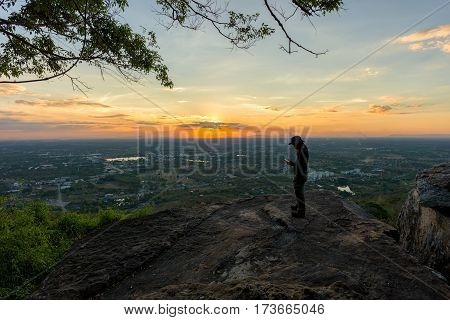 Man traveler is using digital phone on cliff with beautiful landscape sunset over cliff and city