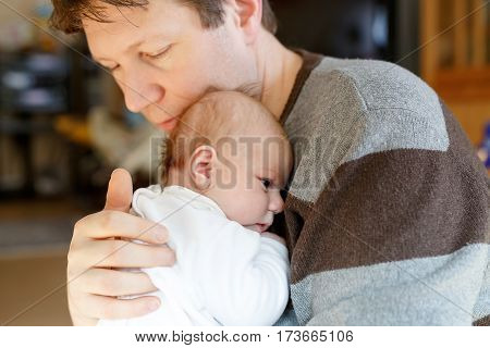 Happy proud young father having fun with newborn baby daughter, family portrait togehter. Dad with baby girl, love. New born child looking on dad. Bonding, family, new life