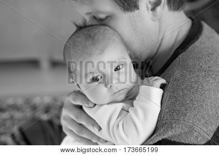 Happy proud young father having fun with newborn baby daughter, family portrait togehter. Dad with baby girl, love. New born child looking on dad. Bonding, family, new life. Black and white