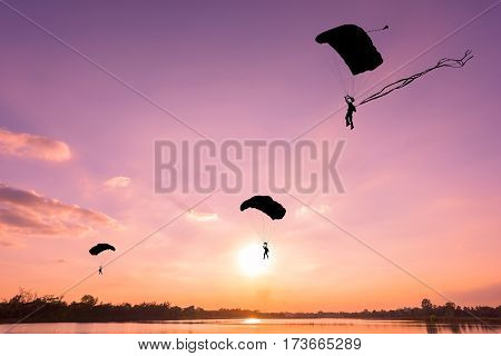 Silhouette of parachute on sky sunset background