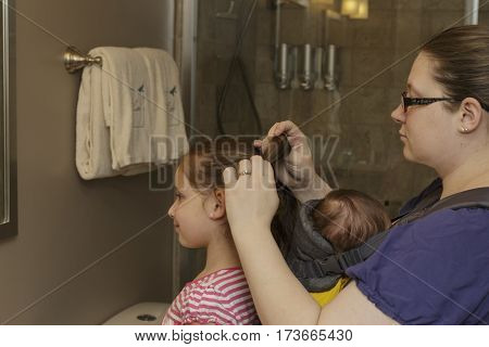 mother helping her daughter with her hair with baby strapped to her chest