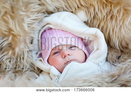 Portrait of newborn baby in warm winter clothes. Beautiful cute girl in warm overall, cap. Peaceful child sleep during outdoor walk.
