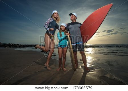 Family Having Fun with surfboards on the  Beautiful Sunny Morning Beach