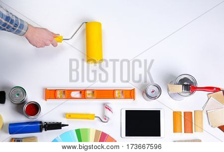 Decorator's hand with paint roller. Color swatches and tools on work table