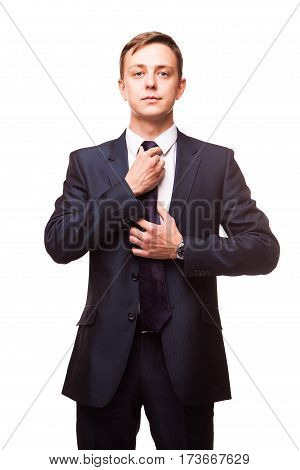 Stylish young man in suit and tie. Business style. Handsome man is standing, looking at the camera and fixing his tie.