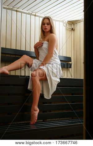 Gorgeous longhaired young blonde wrapped in white towel posing in sauna interior