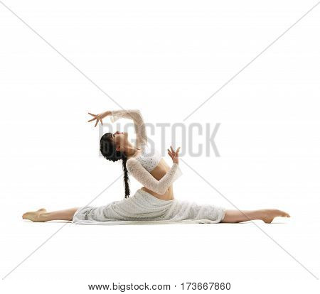 Young gymnast dressed in white top and long skirt sitting in a graceful split in studio
