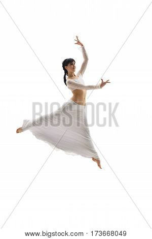 Young gymnast dressed in white top and long skirt shot in a graceful jump in studio