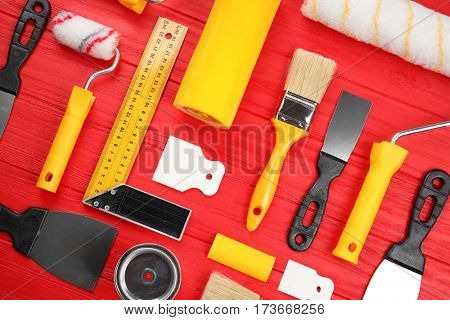 Composition of decorator and house renovation tools on wooden table