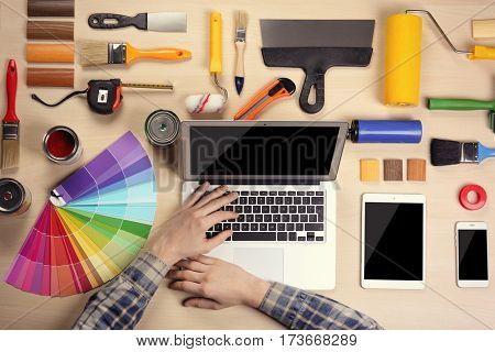 Decorator's hands typing on a laptop. Color swatches and paint tools on work table