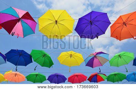 Colorful umbrellas background. Coloruful umbrellas urban street decoration. Hanging Multicoloured umbrellas over blue sky.