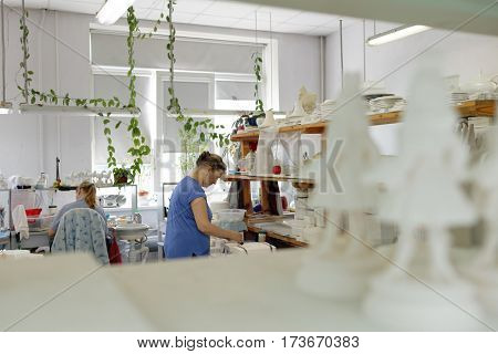 ST. PETERSBURG, RUSSIA - AUGUST 9, 2016: Workers of Imperial porcelain manufactory at workplace. Founded in 1744 by order of Empress Elisabeth, now the factory produces about 4000 items