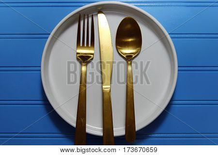 A round white plate with a golden fork knife and spoon cutlery on blue wooden background copy space
