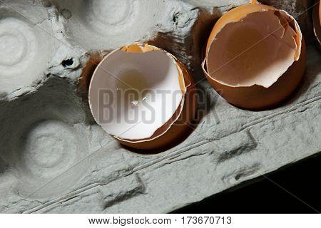 Top view of broken brown egg shells in a carton selective focus.