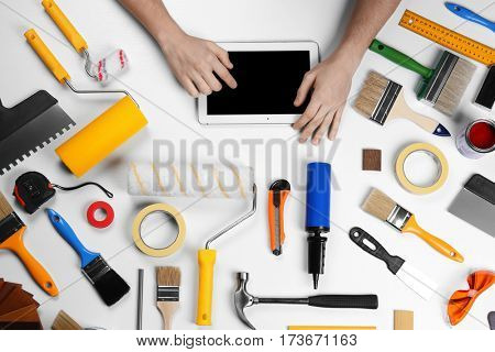 Decorator using a digital tablet. Painting tools all around on table