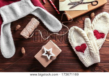 Winter clothes and Christmas decorations on wooden background