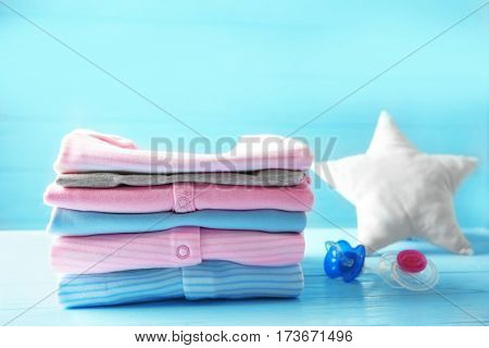 Pile of baby clothes and pacifiers on wooden table