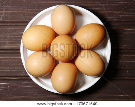 Top view of brown eggs in a white round plate on a wooden background
