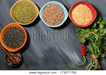 Different types of lentils in bowls (yellow brown green red french green black lentils) with copy space
