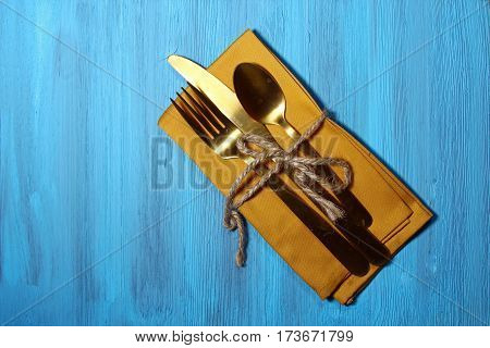 Napkin with cutlery on a wooden blue background with copy space.
