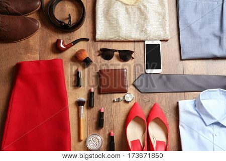 Flat lay set of male and female clothes and accessories on wooden background