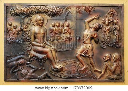 KOLKATA,INDIA - FEBRUARY 09, 2016: Who digs a ditch falls in it. Gosalaka hurls Tejolesya - fiery flame to burn Mahavira but he himself is burnt, bass relief on the wall of Jain Temple in Kolkata