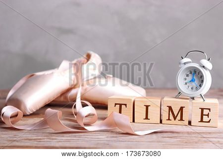 Cubes with alarm clock and pointe shoes on wooden table. Time concept