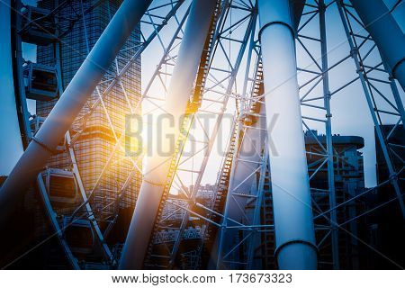 Big ferris wheel with cityscape in background.