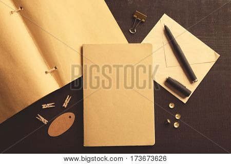 Blank sketchbook and stationery on black background