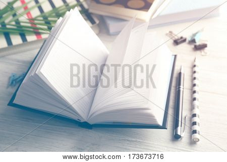 Notebook and accessories on white wooden table