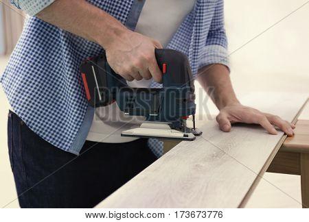 Man cutting laminate board with jigsaw