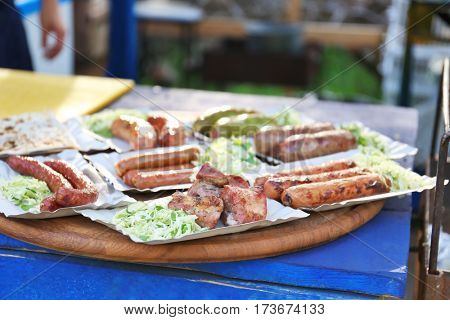 Grilled sausages on wooden table, outdoors