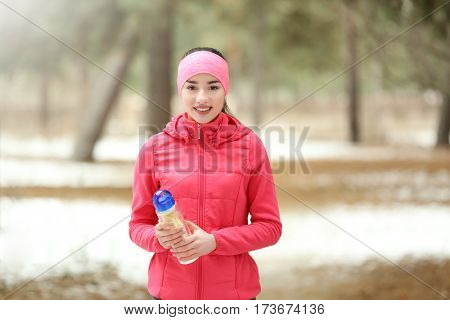 Young woman wearing sportswear with bottle on winter park background