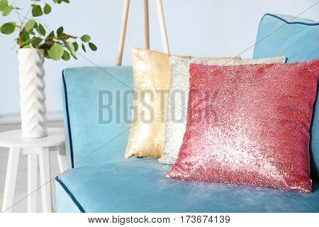 Three shiny decorative pillows on cozy sofa