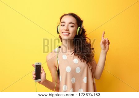 Beautiful young woman in headphones listening to music on yellow background