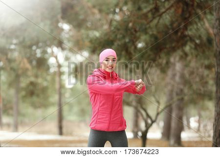 Young woman stretching in winter park